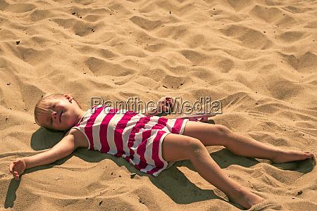 baby girl lying on sand adorable