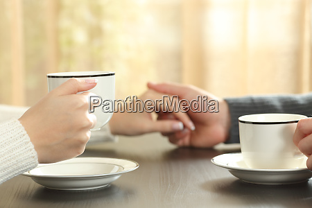 couple holding hands with coffee cups