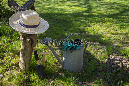 straw sunhat with watering can and