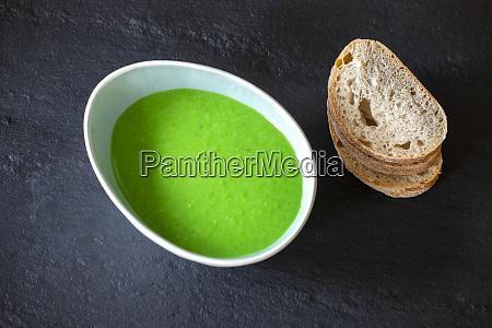 creamy pea soup on black slate