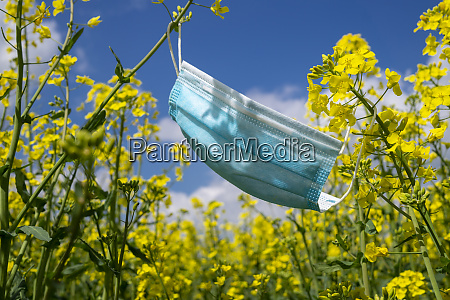 surgical face mask hanging on yellow