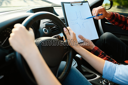 woman and man with checklist driving