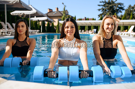 smiling woman with dumbbells in pool