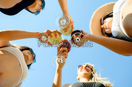 women in swimsuits clink glasses with