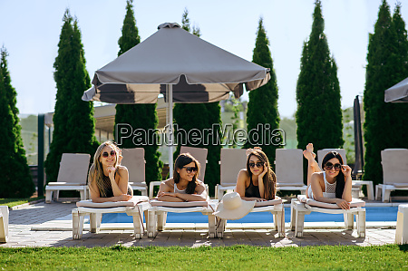 pretty women sunbathing with coctails on