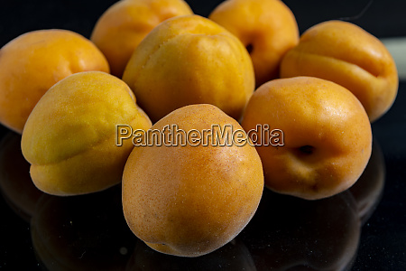 apricots against a black background with