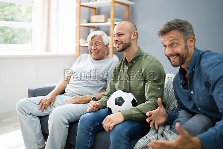 three generation sport fans watching football