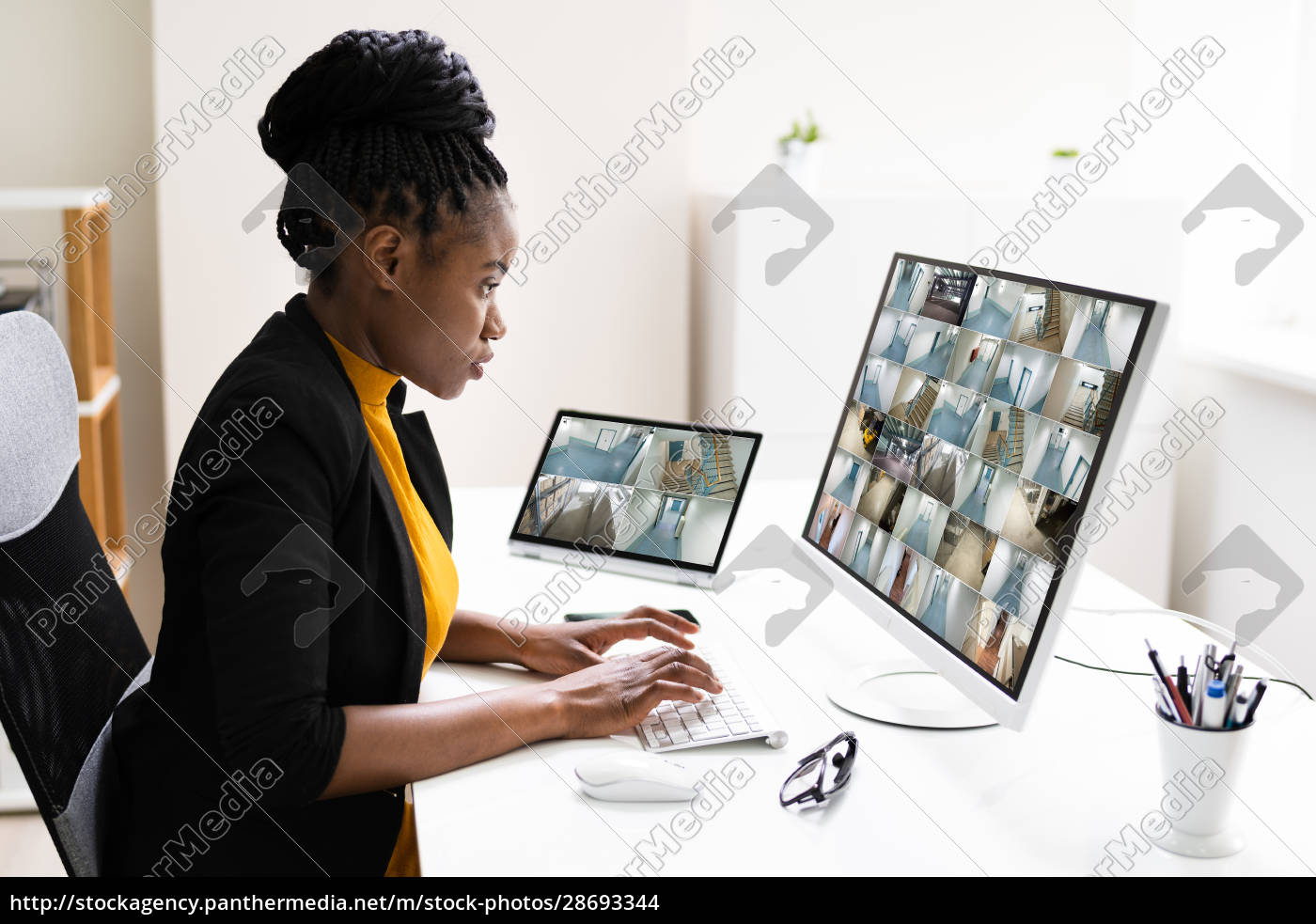 businesswoman, watching, cctv, footage, of, office - 28693344