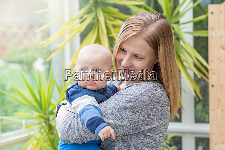 smiling mother is holding her son