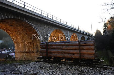 wooden cargo under railway bridge