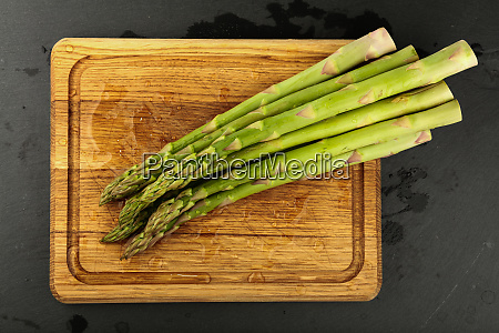 fresh green washed asparagus on wooden