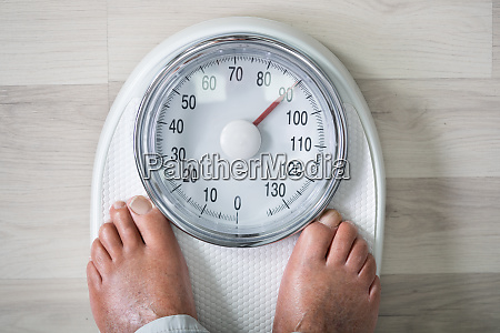 man feet on weight scale