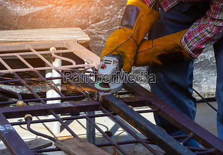 worker grinding hollow structural steel with