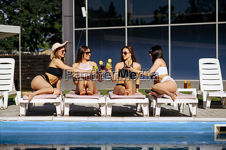 pretty women in swimsuits sunbathing with