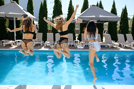 happy women jumps into the pool