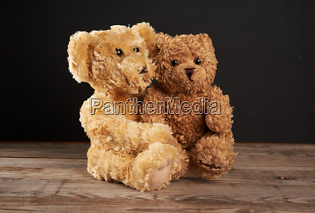 brown teddy bears are sitting on