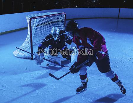 hockey goalie defending net against forward
