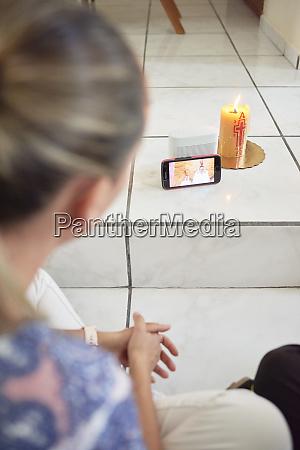 woman attending mass on cellphone