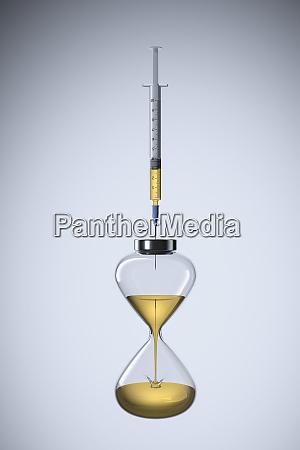 studio shot of hourglass and syringe