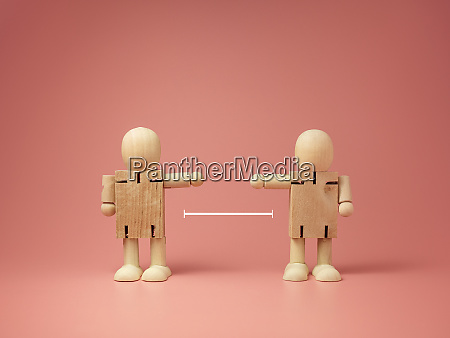 two wooden doll on pink background