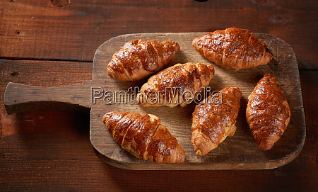 baked croissants on a wooden brown