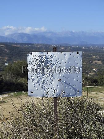 bullet holes in blank white sign