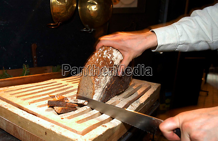 cutting brown bread with a knife