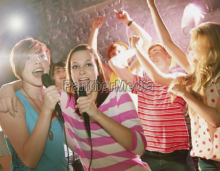 happy teenage friends singing karaoke at