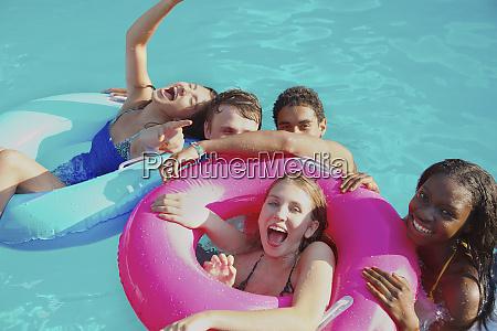 portrait playful teenage friends enjoying pool