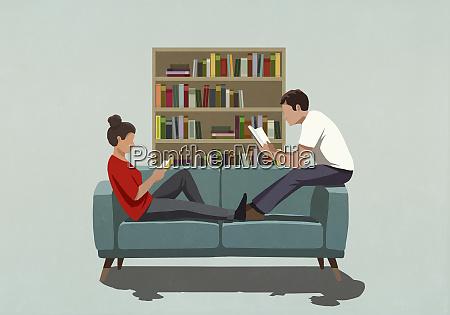 couple reading books on sofa at