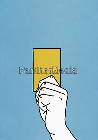 hand holding yellow card