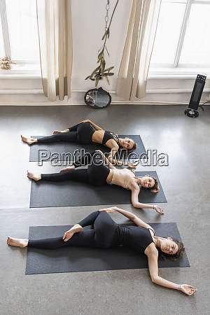 young women practicing supine spinal twist