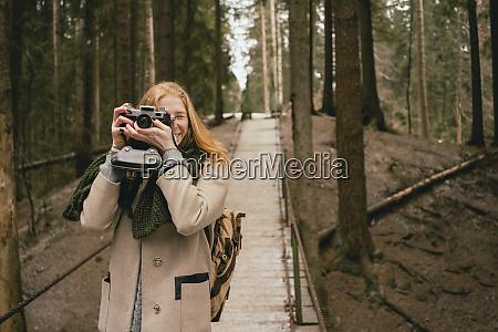 portrait woman using retro camera on