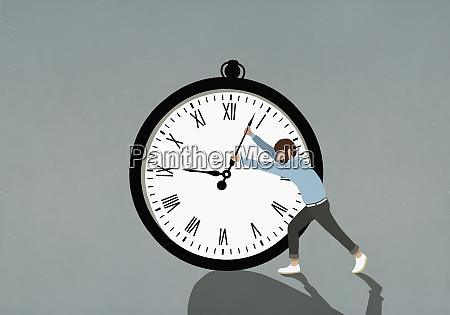 man pushing hands of large stopwatch