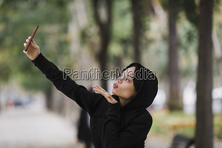 confident playful woman taking selfie with