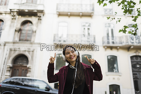 portrait playful cool woman listening to