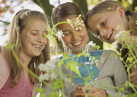 smiling curious girls with magnifying glass