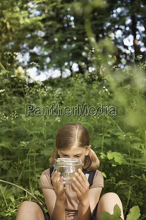 curious girl with insect jar in