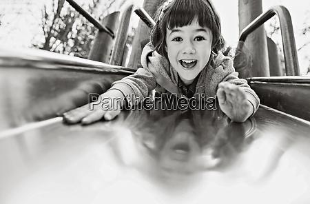 portrait playful girl on playground slide