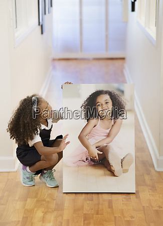 girl looking at printed portrait of