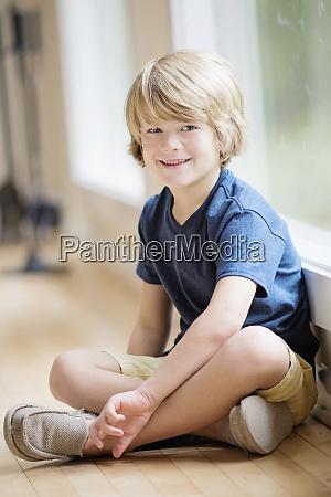 portrait smiling blonde boy sitting at