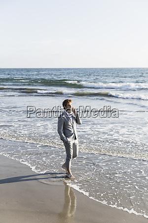 barefoot businessman talking on smart phone