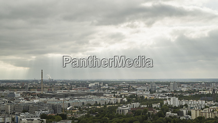 sunbeams in clouds over berlin cityscape