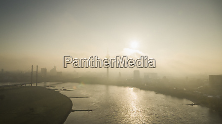 sunset over silhouetted duesseldorf cityscape and