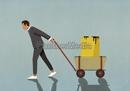 businessman pulling barrel of oil in