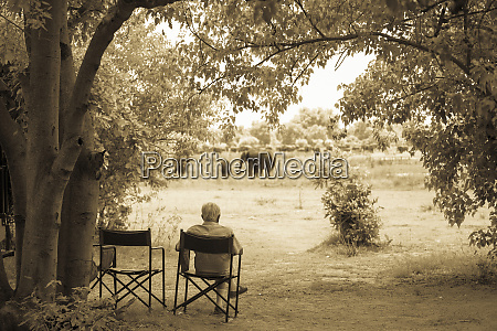 senior man in a chair observing