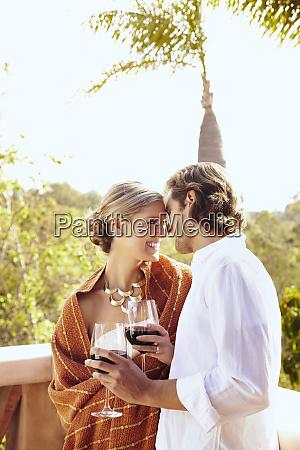 glamorous caucasian couple drinking red wine