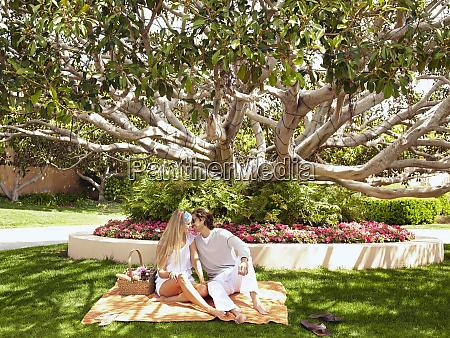 caucasian couple kissing and having picnic