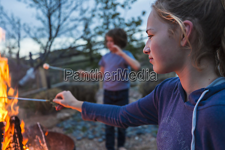 a teenage girl making smores with