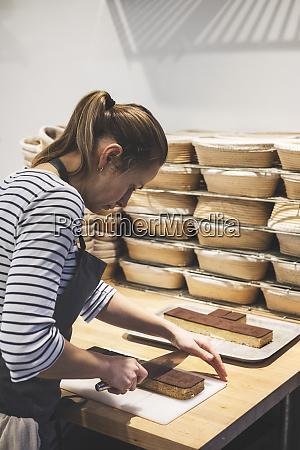 a specialist bakery a baker cutting